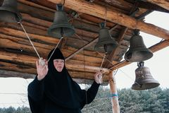 Nun bell-ringer in orthodox church. Starosillia, Volyn / Ukraine - February 04 2009: Woman bell-ringer in orthodox church bell tower Royalty Free Stock Photo