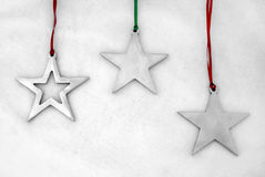 Starry night. Silver, star-shaped holiday ornaments on red and green ribbons Stock Image