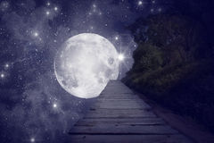 Starry Night. A surreal image of a walkway and a big and bright moon in front. Grain added stock image
