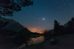 Starry night with blood moon at alpine lake Stock Photo