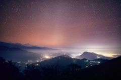 Starry Night in Himalayas. Lights of Pokhara city and villages at night starry sky at mountain range of Annapurna, Nepal Royalty Free Stock Photo