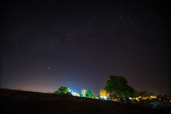 Starry night over village on mountain. Royalty Free Stock Photography