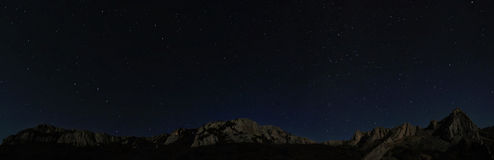 Starry night sky above rocky cliffs Royalty Free Stock Photography