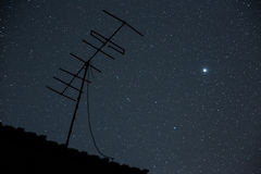Starry night sky with antenna and Jupiter - symbol of alien comm Royalty Free Stock Images