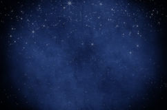 Starry Night Sky Background. Night sky background texture of twinkling white stars, sprinkled on deep blue parchment paper with vignette Stock Image
