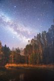 Starry night sky in a forest. Near the lake stock photo