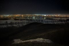 Starry night sky over the city and the river during spring flood. Landscape with a long exposure Royalty Free Stock Photo