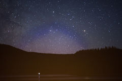 Starry night sky over mountain lake and forests. In summer Royalty Free Stock Image
