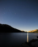 Starry Night sky over smooth lake with Car Light reflecting of surface. Car light reflection on smooth lake, starry night sky above Royalty Free Stock Photo