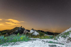 Starry night sky over the white chalky mountains. Natural landscape. Night view of the chalk hills.
