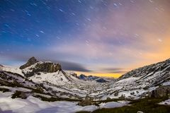 Starry night sky in snowy alpine mountains. Winter in Swiss Alps, Switzerland. Star trails at night above high altitude alpine landscape with snow covered Stock Image