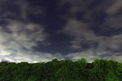 Starry Night, White clouds, many stars, green forest. The edge of the forest. Royalty Free Stock Image