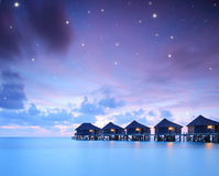Starry skies over water villa cottages on island of Kuredu, Mald Royalty Free Stock Images