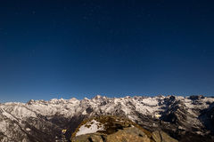 The starry sky above the Alps in winter under moonlight Stock Photography