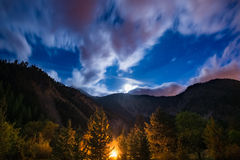 The starry sky with blurred motion clouds and bright moonlight, captured from larch tree woodland, glowing by burning fire. Expans. Ive night landscape in the Royalty Free Stock Photo