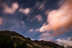 The starry sky with blurred motion colorful clouds and bright moonlight. Expansive night landscape in the European Alps. Vega Star Stock Photo