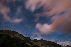 The starry sky with blurred motion colorful clouds and bright moonlight. Expansive night landscape in the European Alps. Vega Star Royalty Free Stock Photos
