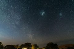 The starry sky and the majestic Magellanic Clouds, outstandingly bright, captured in Africa. Acacia trees and straw hut in the for Royalty Free Stock Photos