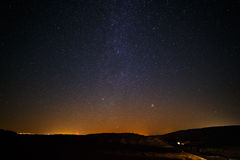 Starry sky and Milky Way  above the lighted lanterns city. Royalty Free Stock Image