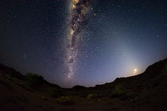 Starry sky and Milky Way arc, outstandingly bright, with rising moon, captured from the Namib desert in Namibia, Africa. The Small. Magellanic Cloud on the left Stock Photo
