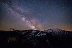Starry sky with milky way over Caucasian mountains and observatory.  Stock Photos