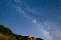 The starry sky and the Milky Way over the mountains and the fore Stock Image
