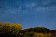 The starry sky and the Milky Way over the mountains and the fore Royalty Free Stock Image