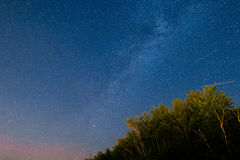 The starry sky and the Milky Way over the mountains and the fore Stock Photography