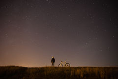 Starry sky, night photography, astrophotography, the silhouette of a man. A man standing next to a mountain bike on the background of a starry sky, the white royalty free stock images