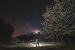 starry sky, night photography, the silhouette of a man standing next to a green meadow with forest trees yellow dressed. Masalli A Royalty Free Stock Photo