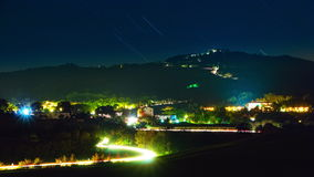 Starry Sky and Night Traffic. Time Lapse 4k. Summer night. Stars in the sky. A small town on the hillside. Vehicular traffic on a winding road. Time Lapse 4K stock footage