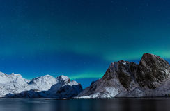Starry sky with northern lights ofer steep rocky mountains in no Stock Photo
