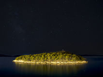 Starry sky over the island. At night with lights reflecting on see in foreground, Croatia royalty free stock photos