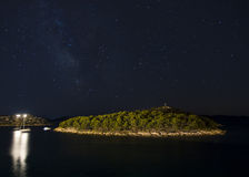 Starry sky over the island. At night with lights reflecting on see in foreground, Croatia royalty free stock photo