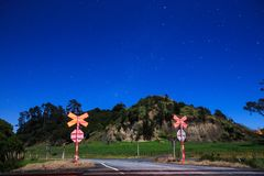 A starry sky in the Southern Hemisphere, seen from a rail crossing. The night sky as seen in the Bay of Plenty, New Zealand, with the land illuminated by royalty free stock images
