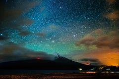 Volcano of Osorno. Starry sky and the volcano of Osorno with clouds highlighted by town, Chile. High level of noise royalty free stock photo