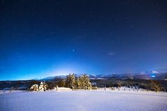 Starry winter night in the mountains. The sky is full of bright stars above the snow-covered valley and mountain peaks. Winter night landscape in blue tones royalty free stock images