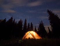 Stars above the mountains with tent highlighted Royalty Free Stock Photography