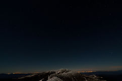 Stars above snowy autumn mountain ridges. And city lights royalty free stock image