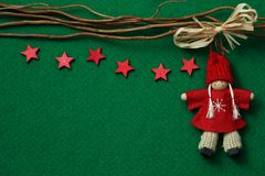 Stars and angel on felt background. Red stars and angel on green felt background stock photo