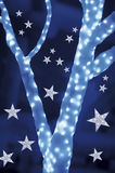 Stars on background of defocused blue lights and tree Stock Photos