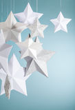 Stars Border. Handmade paper star decorations hanging in front of a blue green background stock image
