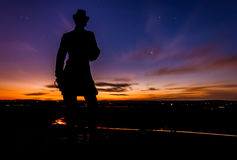 Stars and clouds move behind a statue on Little Round Top in Get royalty free stock photos