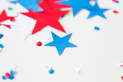 Stars confetti on american independence day party. American independence day, celebration, patriotism and holidays concept - red and blue paper stars confetti on Stock Image