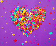 Stars confetti on a purple background, a heart Royalty Free Stock Photos