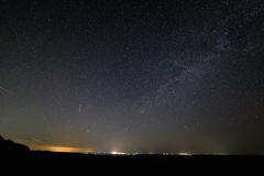 Stars in dark night sky with city lights on the horizon. royalty free stock image