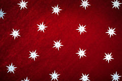 Stars on dark red textile, christmas background Royalty Free Stock Image