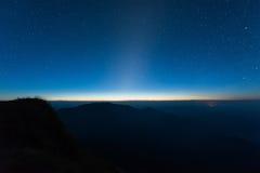 Stars illuminated above the dark silhouette mountain before sunrise.  royalty free stock photos
