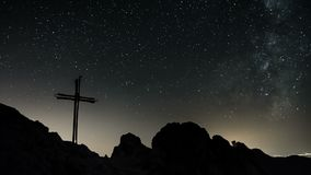 Stars with milky way galaxy moving over cross in top of the mountains Time lapse. Stars with milky way galaxy moving in starry night sky over cross and rocks in stock footage