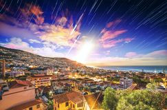 Stars and moon sunrise Funchal. Beautiful long exposure stacked view of the skyline cityscape of the city Funchal on the island Madeira at sunrise in summer with stock images
